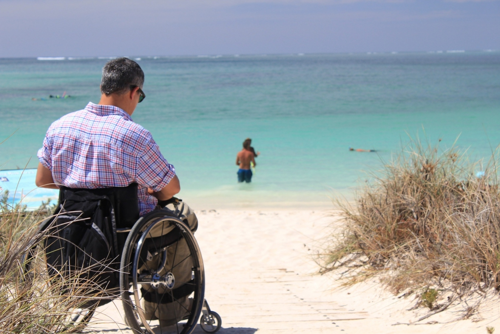 Man On Wheelchair At The Beach